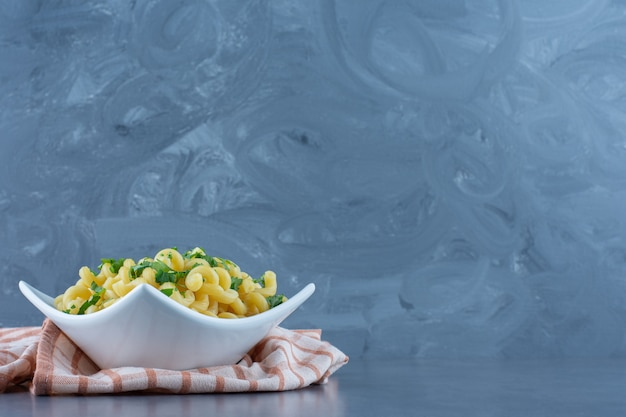 Boiled macaroni with greens in white bowl.