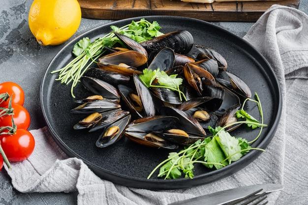 회색 배경에 접시에 파슬리와 재료를 넣은 마늘 소스에 삶은 홍합
