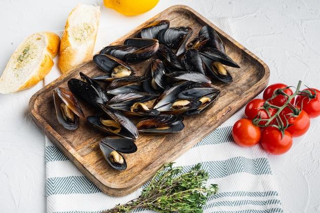 パセリと材料を添えたガーリックソースで煮たムール貝、木製トレイ、白いテーブル