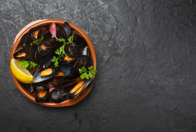 Boiled mussels with lemon in a bowl on dark space