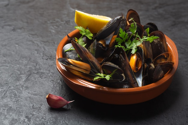 Boiled mussels with lemon and parsley in a bowl on dark space, close up