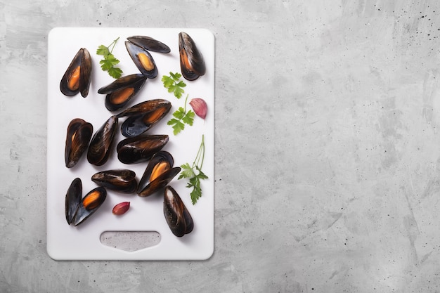Boiled mussels with spices on gray stone space, vertical orientation with copy space