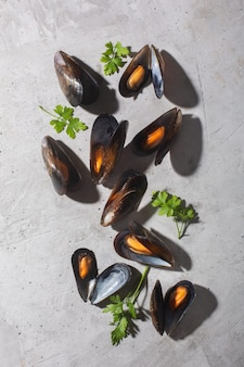 Boiled mussels with spices on gray stone space, vertical orientation