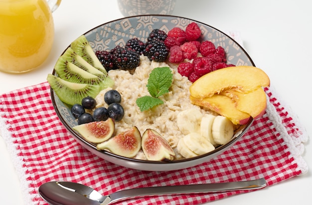 Вареные овсяные хлопья с фруктами в круглой тарелке на белом столе, здоровый завтрак. вид сверху