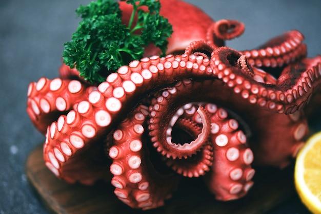Вареные щупальца осьминога с лимоном на тарелке, салат из блюд из осьминога, морепродукты, кальмары, каракатицы