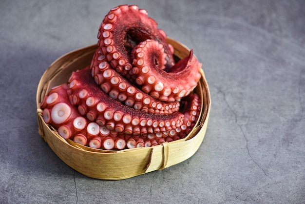 Boiled octopus tentacles on wooden tray, octopus food cooked seafood squid cuttlefish