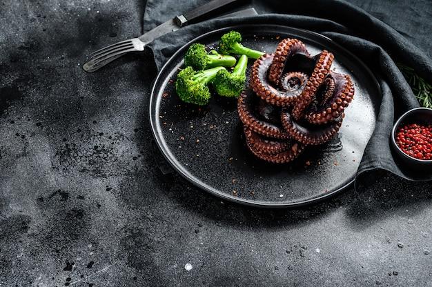 Вареный осьминог с брокколи на тарелке. черный фон