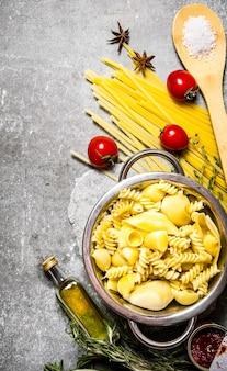 鍋にオリーブオイルとトマトを入れて茹でたパスタ。石のテーブルの上。上面図