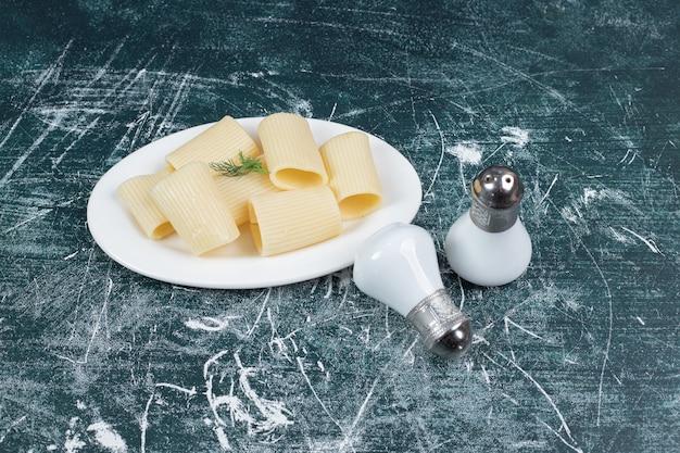 白い皿に塩で煮たパスタ。高品質の写真