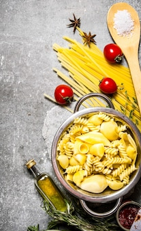 Boiled pasta in the pan with olive oil and tomatoes.  on the stone table. top view