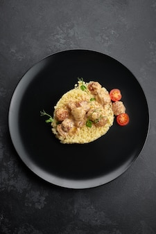Boiled pasta stars with meatballs, cherry tomatoes and microgreen, on a black background