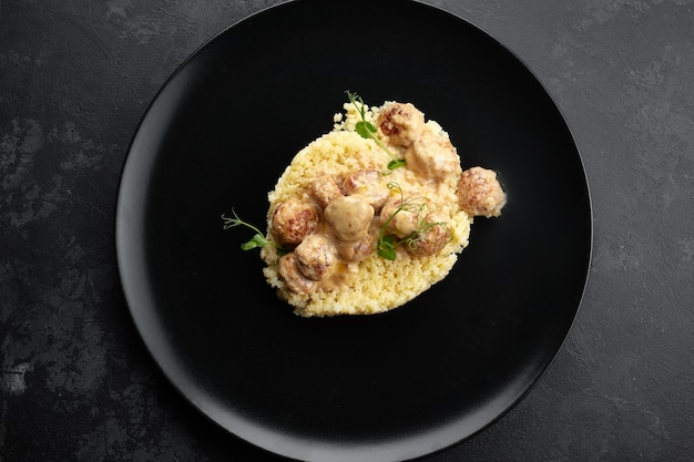 Boiled pasta stars with meatballs and microgreen, on a black background