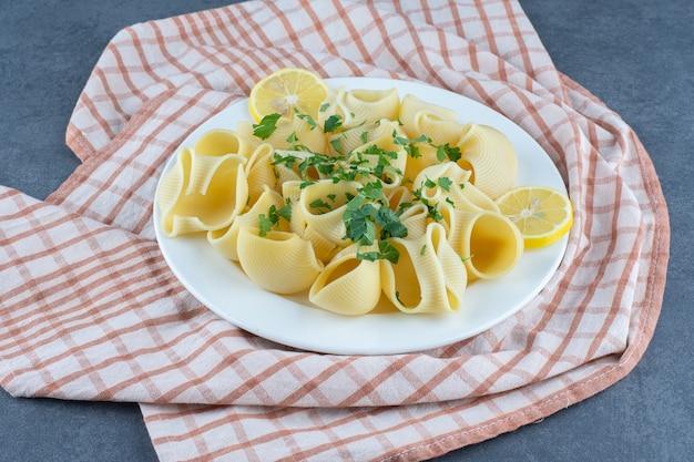 Вареные макароны с ломтиками лимона на белой тарелке.