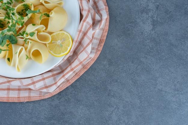 白い皿にレモンスライスを添えたゆでパスタ。