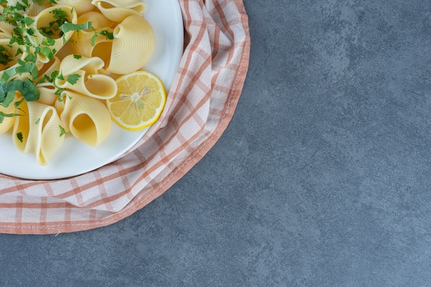 Boiled pasta with lemon slices on white plate.