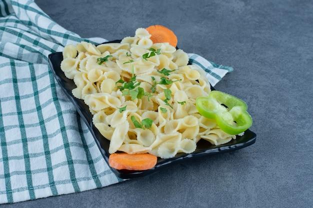 검은 접시에 야채와 삶은 파스타.