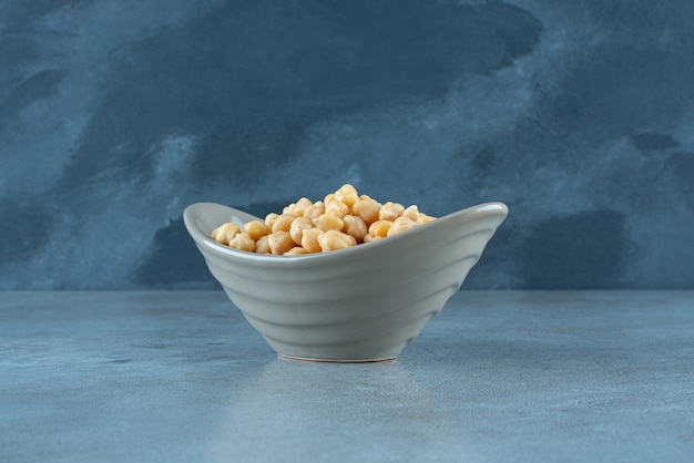 青い背景のカップでゆでたエンドウ豆。高品質の写真