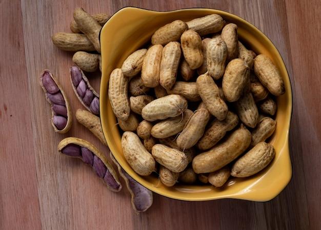 검정색과 노란색 그릇에 삶은 땅콩 (amendoin cozido, sergipe, nordeste, 브라질)과 삶은 땅콩이 펼쳐져 나무 배경에 그릇 외부에 열립니다. 평면도.