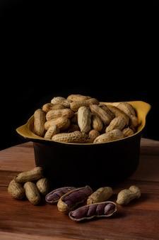 검정색과 노란색 그릇에 삶은 땅콩 (아멘도 인 코지도, 세르 기페, 노르 데스테, 브라질)과 삶은 땅콩이 그릇 바깥쪽에 펼쳐집니다.