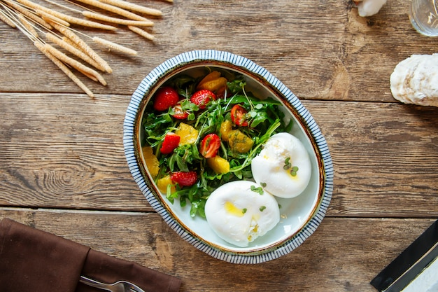 Boiled poached eggs with fresh vegetable salad