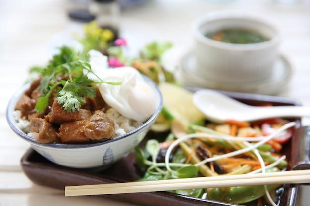 Жаркое из отварной свинины с рисом и яйцом на деревянном фоне