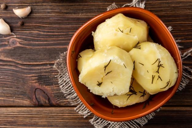 ダークウッドの茶色のボウルに茹でたジャガイモ
