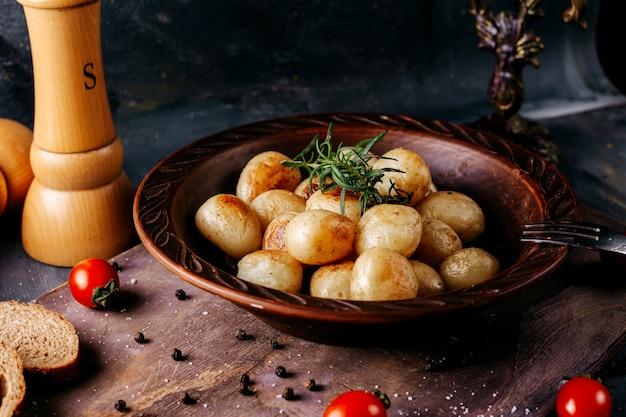 Вареный картофель вместе с зеленой травой внутри коричневой круглой пластины на темной поверхности