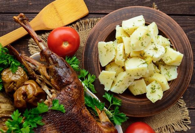 Картофель отварной в глиняной посуде и жареный гусь. вид сверху