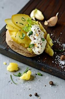 Картофель отварной в кожуре в миске со специями и зеленью