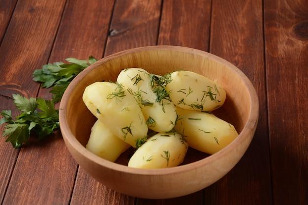 허브와 함께 나무 그릇에 삶은 감자. 소박한 스타일