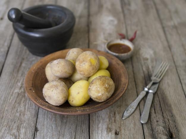 Картофель отварной в кожуре. целиком с красным перцем, солью и острым соусом на глиняной тарелке, старый деревянный стол, деревенский стиль. закройте, скопируйте пространство. вид сверху.