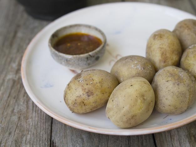 皮に茹でたジャガイモ。全体に赤唐辛子、塩、スパイシーソースを白いプレートに載せ、古い木製のテーブル、素朴なスタイル。クローズアップ、スペースをコピーします。