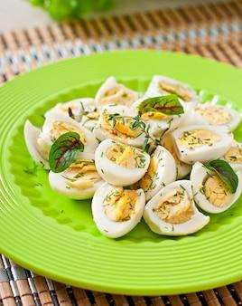 Вареные яйца перепелиные половинки на зеленой тарелке
