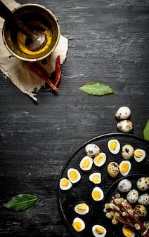 黒い木製のテーブルの乳鉢で挽いたスパイスの柳の枝にゆでウズラの卵。