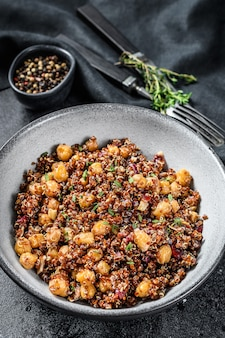 Boiled quinoa with chickpeas. healthy food, diet. black background. top view.