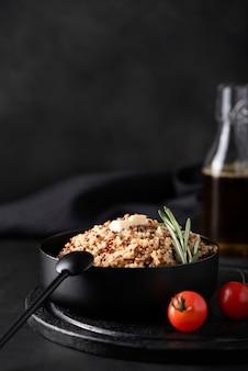 검은 그릇에 향신료와 야채를 곁들인 삶은 노아
