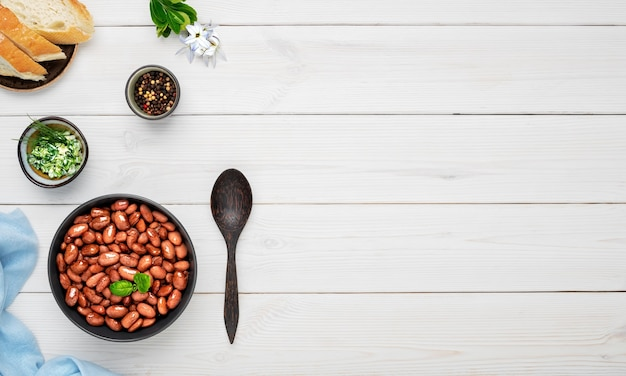 Boiled red beans decorated with basil leaves in a black bowl