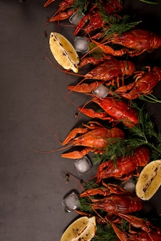 Boiled red crawfish ready to eat with lemon slices and ice cubes on a black surface