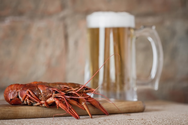 Boiled red crawfish on the wooden surface against a mug of beer background.