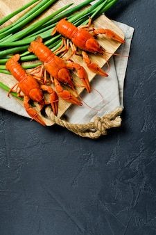 Boiled red crayfish on a wooden chopping board.