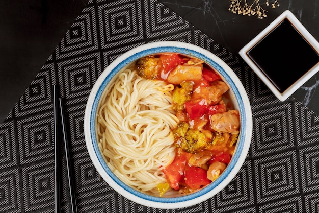 Boiled rice noodles with broccoli, chicken and bell pepper in sweet and spicy sauce