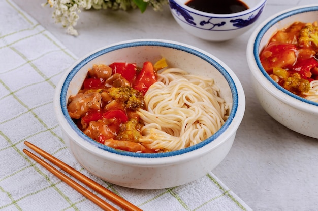 Boiled rice noodles with broccoli, chicken and bell pepper in sweet and spisy sauce. asian food.