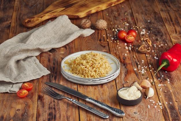 Вареный рис на тарелке на деревянном столе
