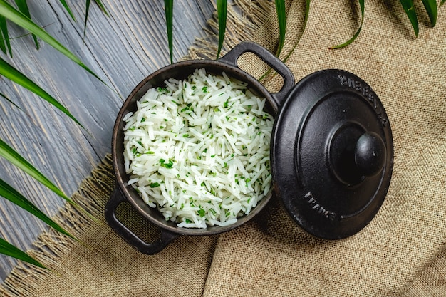 Boiled rice with herbs in a pan on a wooden table