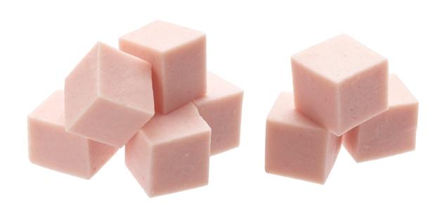 Кубики вареной колбасы на белом фоне
