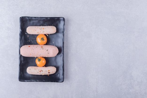 Вареные сосиски и помидоры черри на черной тарелке.
