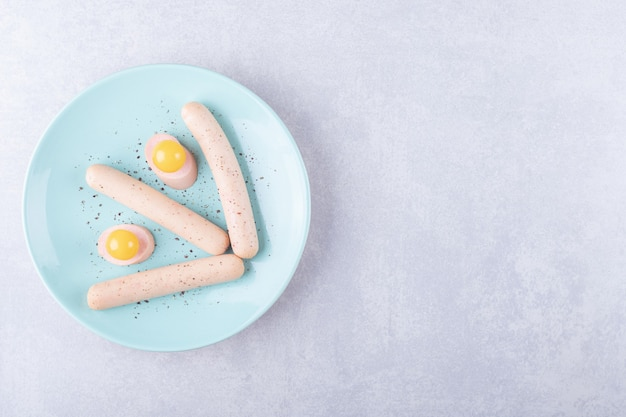 파란색 접시에 삶은 소시지와 달걀 노른자.