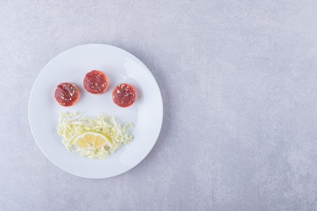 Вареные сосиски и тертый сыр на белой тарелке.