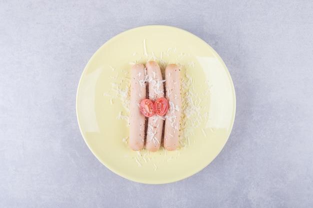 노란색 접시에 토마토로 장식 된 삶은 소시지.