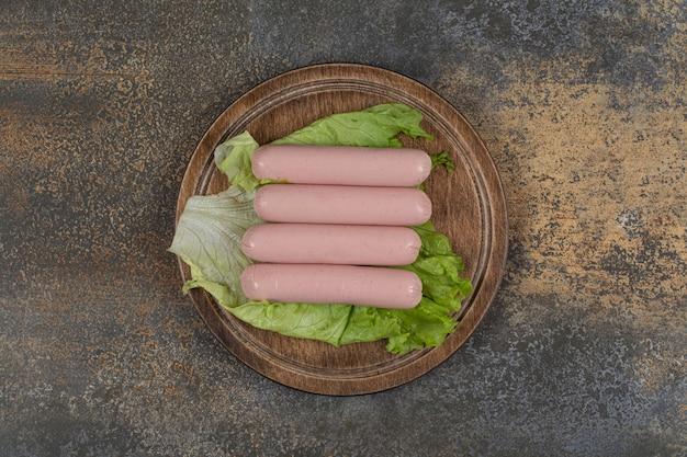 Salsicce bollite e lattuga su tavola di legno.